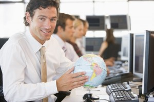 Businessman in office space with a desk globe